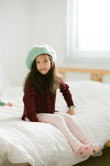 Cute little girl is sitting on the bed Relaxing Comfortable Kids Girl Cute One Person Child Girls Bed Childhood Winter Furniture Real People Clothing Women Cold Temperature Females Front View Long Hair Bedroom Portrait Full Length Warm Clothing Looking At Camera Hair My Best Photo