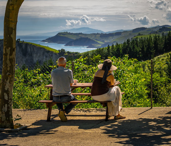 Endless view - endless love. Beautiful senior couple sitting outside in summer nature. Rear view. Mountain Two People Nature Real People Beauty In Nature Leisure Activity Plant Tree Rear View Men Scenics - Nature Togetherness Sitting Adult Lifestyles People Shadow Women Mountain Range Couple - Relationship Outdoors Positive Emotion Looking At View Endless View Endless Love