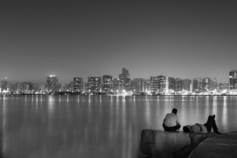 Rear view of men sitting by sea against buildings in city