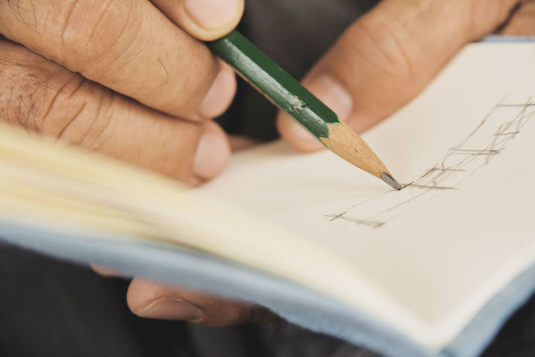 Close-Up Of Man Drawing On Paper