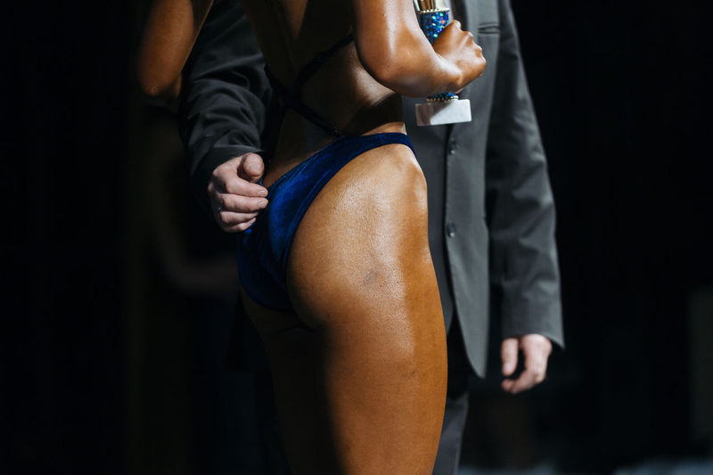 Midsection of businessman standing with female athlete on stage