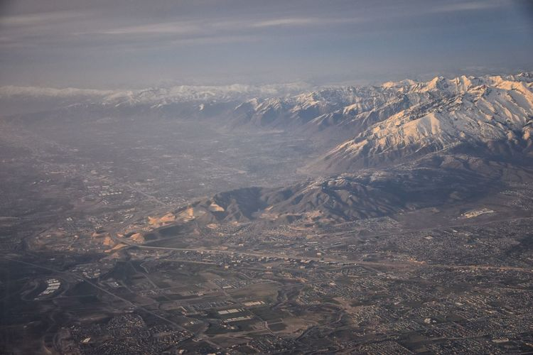 Aerial view from airplane of the Wasatch Front Rocky Mountain Range with snow capped peaks in winter including urban cities of Provo, Farmington Bountiful, Orem and Salt Lake City. Utah. United States. Wasatch Front Rocky Mountains Snow Winter Peaks Aerial Drone  Utah Lake Salt Lake Cloudscape Timpanogos Lone Peak Utah Lake Flight Panorama Banner Copy Space