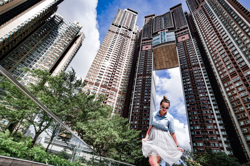 Low angle view of woman standing against buildings in city