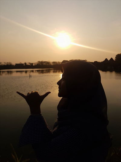 Woman gesturing shaka sign by lake against sky during sunset