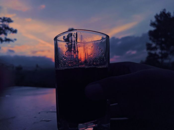 Close-up of beer glass against sunset sky