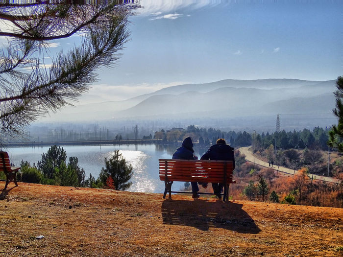 Rear View Of Friends Sitting On Bench Against Lake