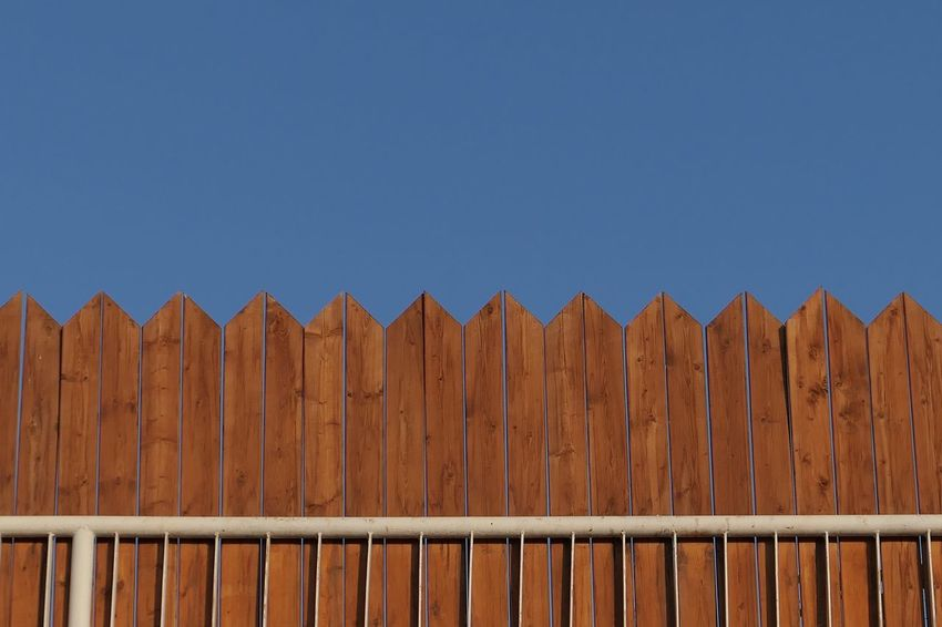 Wood - Material Fence Sky No People Boundary Barrier Clear Sky Day Brown Blue Pattern Security Protection Side By Side Outdoors Sunlight