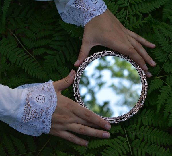 Woman with a mirror in the forest
