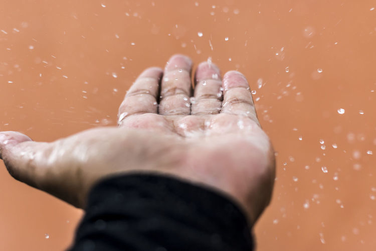 Close-Up Of Water Splashing On Human Palm