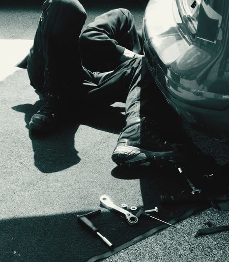 A man lying on the floor working underneath the back of a car. Human Body Part Parked Driveway Mat Blackandwhite Fitting Repairs Hot Day Mechanic Working Tools Tool Form Of Transport Car Outdoors Lying Silhouette Sunlight Shadow Real People One Person Day Men Full Length Lifestyles Transportation Low Section High Angle View Shoe Adult