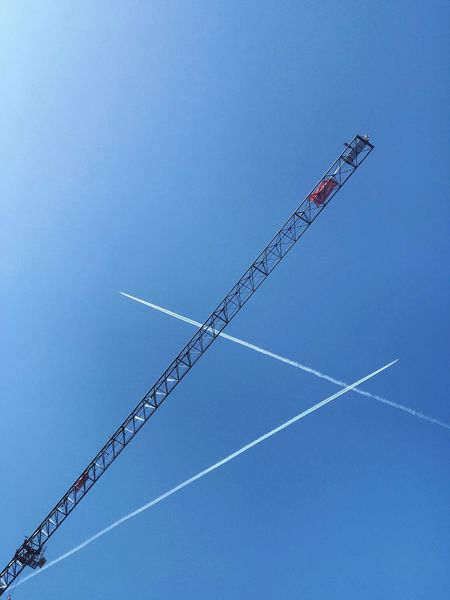Geometry in the sky Sky Low Angle View Clear Sky Nature Blue Vapor Trail Day No People Technology Outdoors Communication Tower Built Structure Machinery Construction Industry Crane - Construction Machinery Visual Creativity