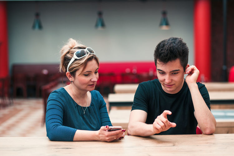 Mother using mobile phone while son gesturing in restaurant