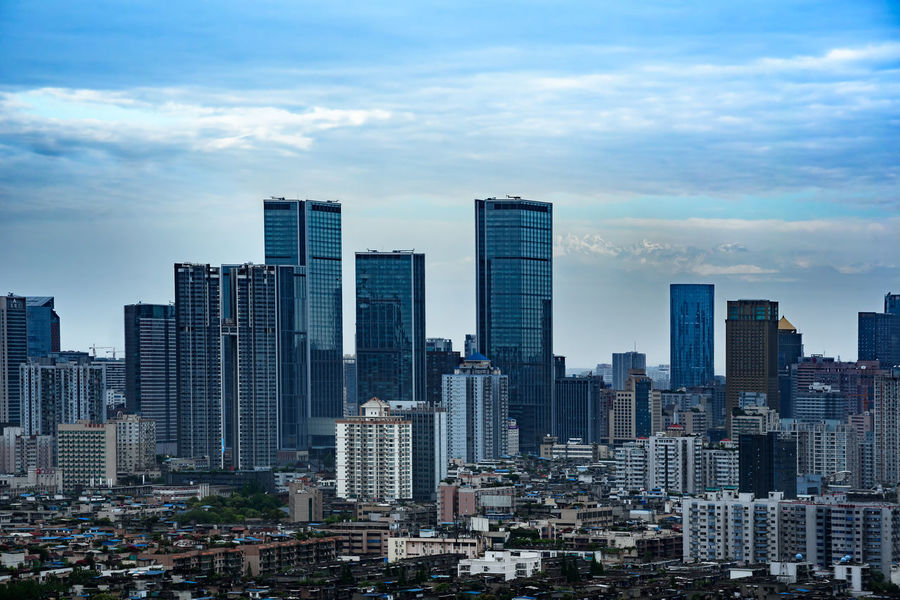 The landmark IFS tower in Chengdu downtown with the snowcapped Mount Xiling. Chengdu City Cloudy Downtown Skyline Arial Building Building Exterior Cityscapes Day Downtown District Finance Landmark Mountain No People Skyscraper Snowcapped Mountain Snowmountain Tower Urban Landscape