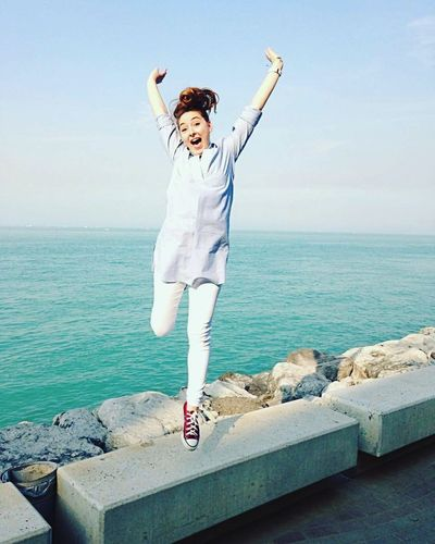 Full Length Portrait Of Happy Woman With Arms Raised Against Sea