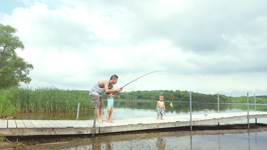 Father fishing while standing with children on pier over lake against cloudy sky