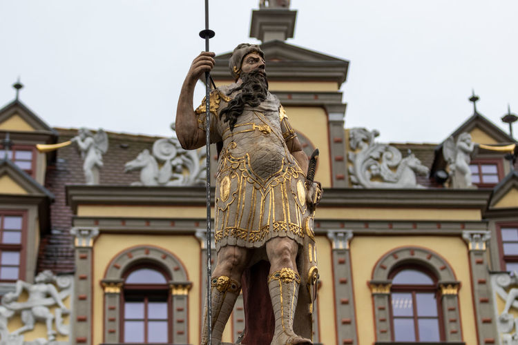 Low angle view of statue against historic building