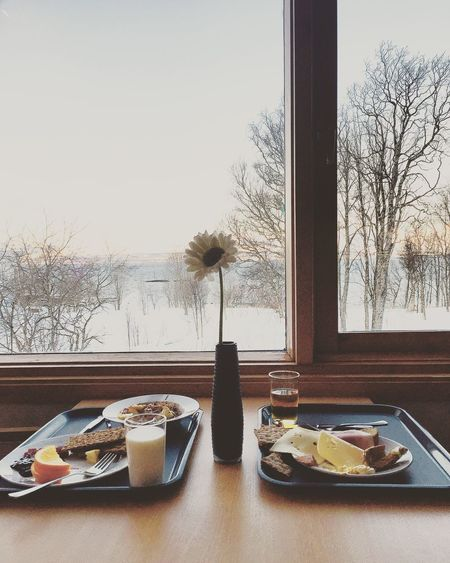 Close-up of fresh breakfast served in tray on table against window