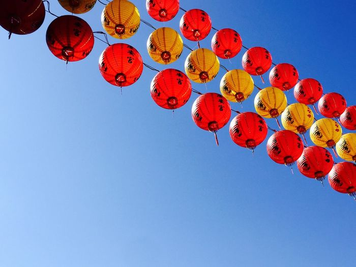 Low angle view of lanterns against clear blue sky