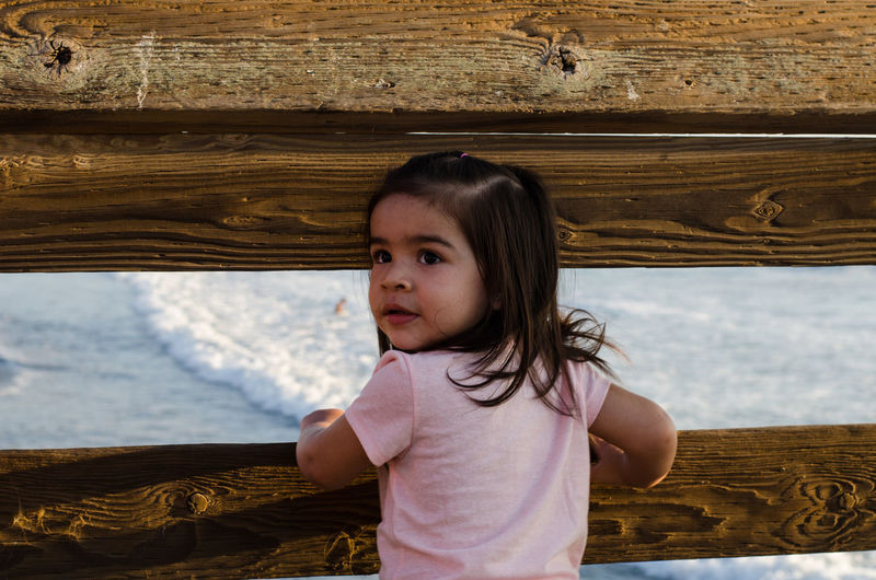Young Hispanic girl standing on a pier, ocean background Carefree Casual Clothing Child Childhood Children Photography Children Portraits Content Day Girls Hispanic Hispanics History Human Face In Front Of Latino Leisure Activity Lifestyles Long Hair Minority Person Tranquility