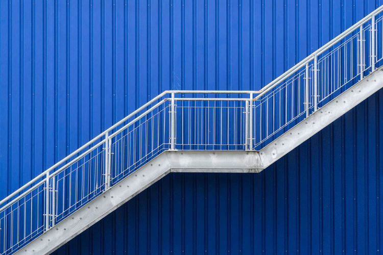 White staircase insolated in blue corrugated metal background Architecture Blue Built Structure Corrugated Iron Day Design Emergency Escape Exit Exterior Design Hand Rail Metal No People Outdoors Pattern Railing Steps Steps And Staircases Texture White Fresh On Market 2017 The Graphic City