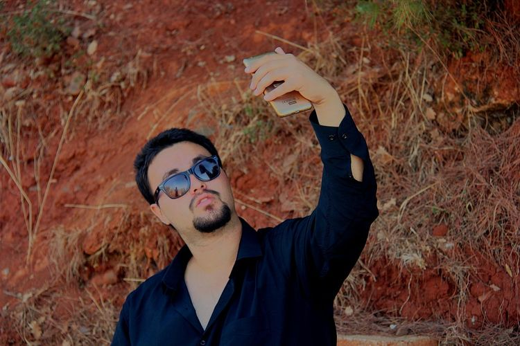 Young man wearing sunglasses while taking selfie with smart phone