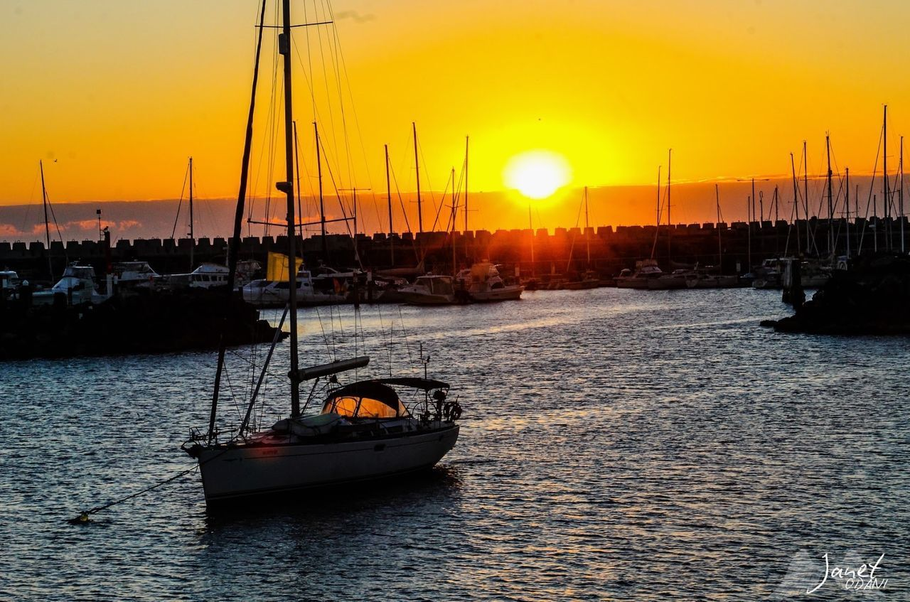 SAILBOATS MOORED IN SEA DURING SUNSET