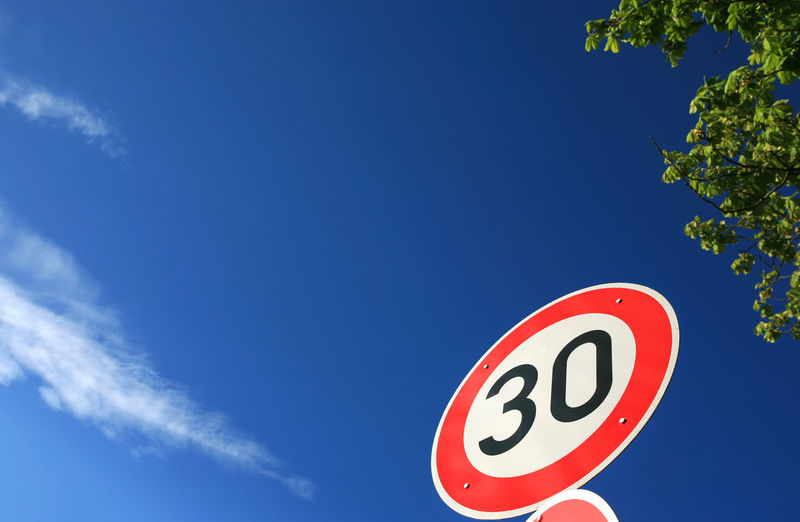 Speed limit traffic sign in front of a blue sky Blue Sign Low Angle View Sky Communication Road Sign No People Road Number Circle Red Outdoors Copy Space Sunlight Symbol Speed Limit Sign Thirty 30 Traffic Sign Concept Anniversary Birthday Slow Speed Maximum
