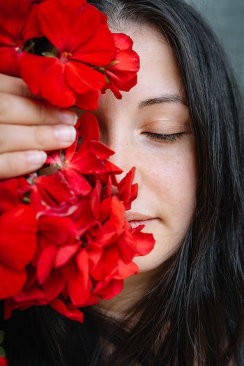 Close-up of woman holding red geranium flower