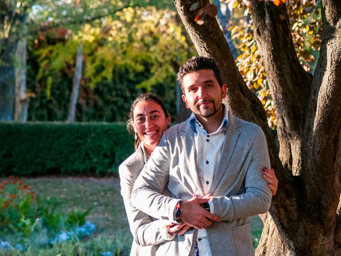 Portrait of smiling couple standing against tree in park