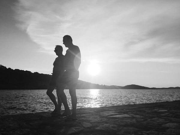 """Beaching"", Veli Losinj, Croatia, 2017. Rovenska Veli Lošinj Croatia Beach Sun Sun Flare Sunset Day At The Beach Two People Togetherness Water Silhouette Walking Discuss Documentary Photojournalism"