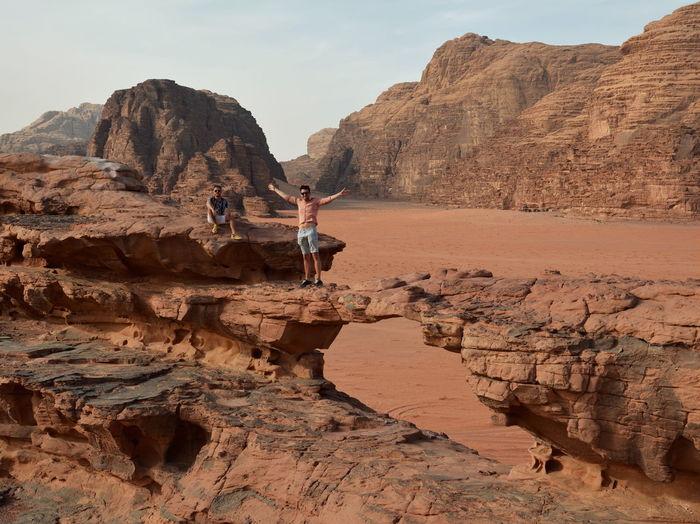 Friends posing on rock formation in wadi rum desert in jordan
