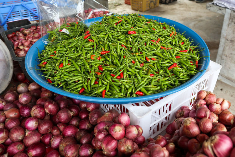 High angle view of chillis and onions in market