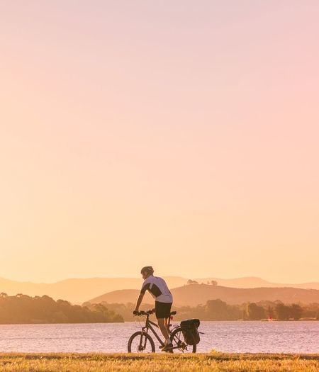Man riding bicycle by lake against sky during sunset