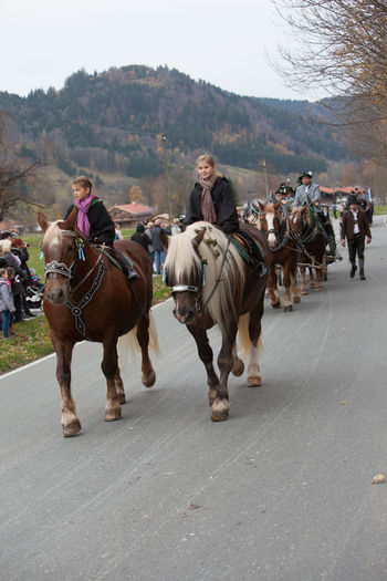 Schliersee, Bavaria - November 5, 2017: Every year on the 1st Sunday in November, the Idyllic Horse procession, named Leonhardi in Bavarian Schliersee takes place in commemoration of Patron St. Leonhard. In traditional clothing and decorated horse-drawn carriages horses and riders move to the church of St. Leonhard Bavaria Leonhard Ride Leonhardi Patron St. Leonhard Schliersee Adult Cart Day Domestic Animals Girls Horse Horse Procession Horseback Riding Idyllic Lifestyles Livestock Mammal Men Nature Outdoors People Real People Sky Togetherness Women