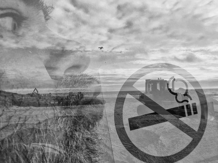Digital composite image of sign on road against sky