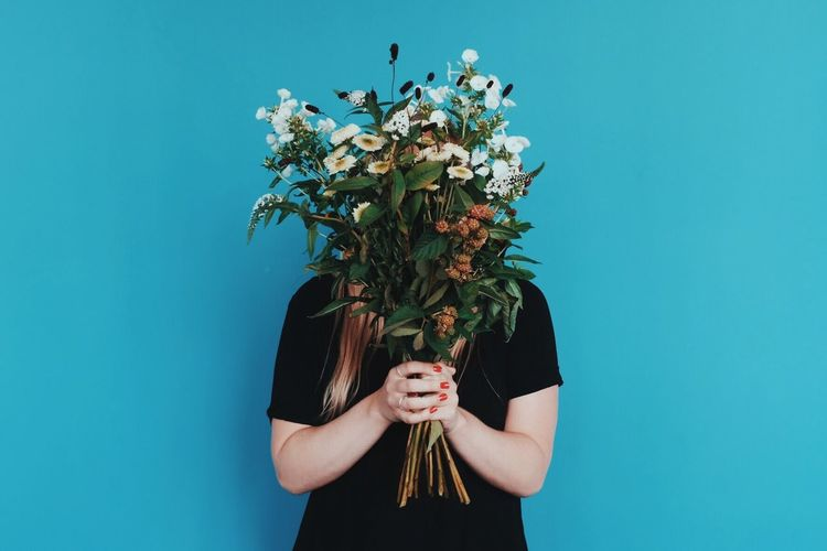 Woman holding bouquet in front of face while standing against blue wall