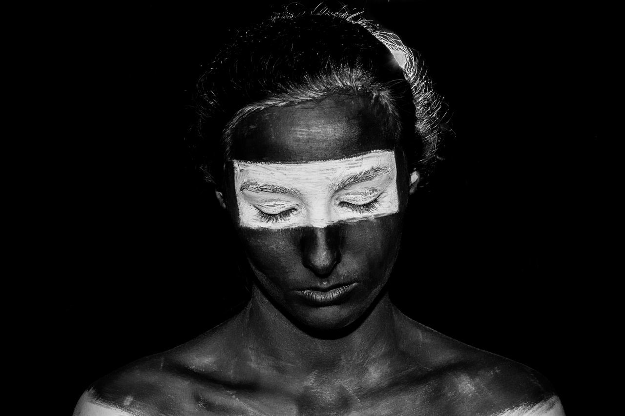 Young Woman With Face Paint Against Black Background