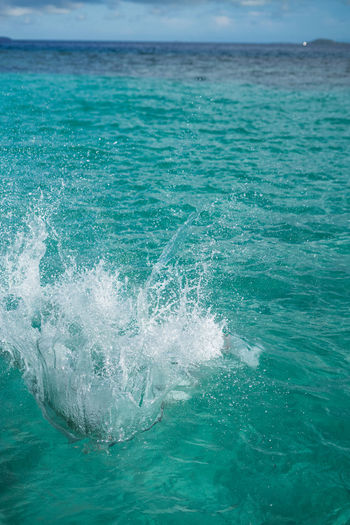 Huge splashing water in the sea from people falling into water, abstract art picture for background.