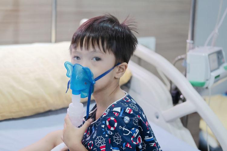 Portrait of cute boy wearing oxygen mask at hospital
