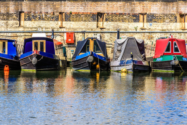 Boats moored in canal by building