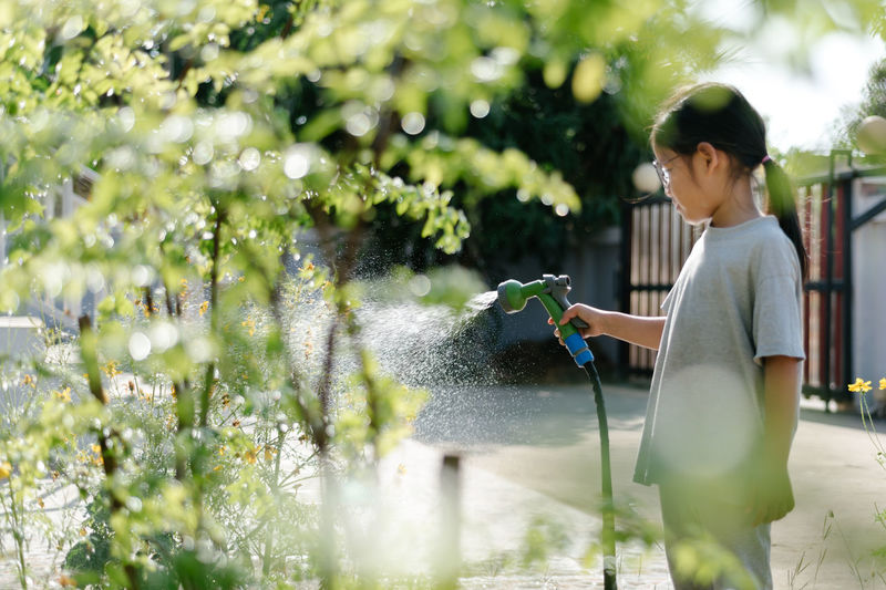 Girl spraying water on plants