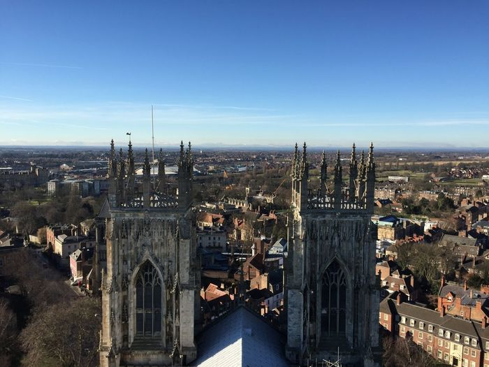 High Angle View Of York Minster Amidst Buildings In City Against Blue Sky