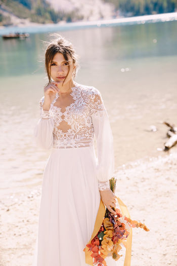 Portrait of bride holding bouquet standing at riverbank