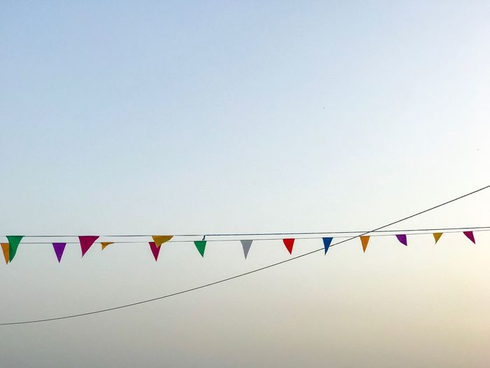Low angle view of bunting flags against clear sky