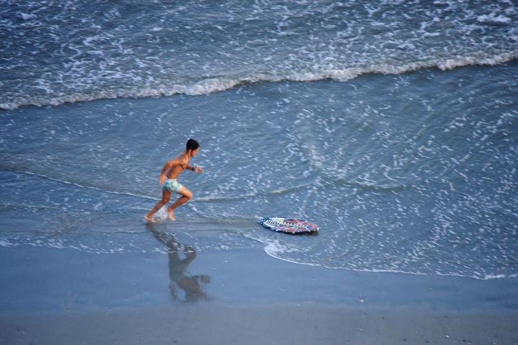 Side view of shirtless man running towards skimboard on shore at beach