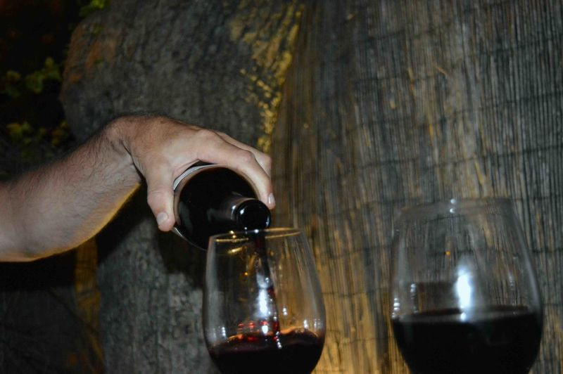Midsection of person pouring wine in glass