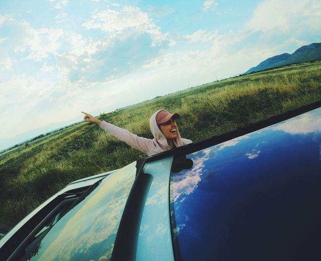 Cheerful young woman with arm raised leaning from car against sky