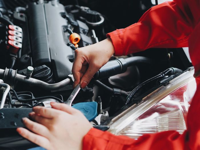 Close up engineering woman fixing car. Adult Day Hand Holding Human Body Part Human Hand Indoors  Men Midsection Mode Of Transportation Occupation One Person Real People Red Selective Focus Shopping Transportation Women Working