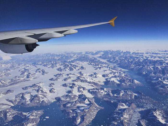 Aerial view of airplane flying over snowcapped mountains against sky