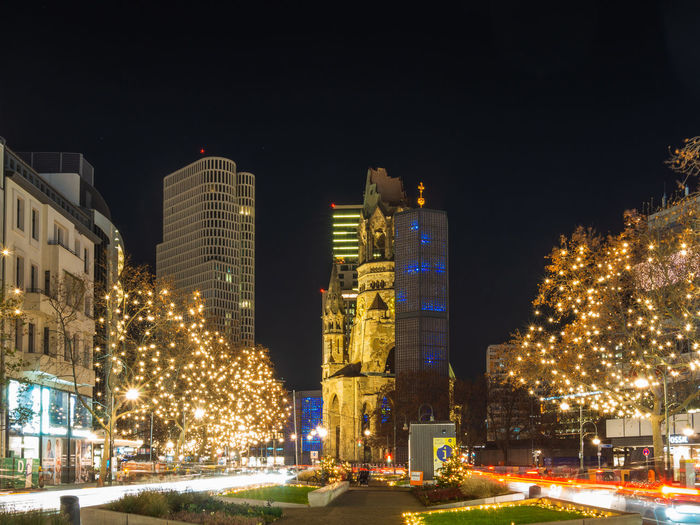 Illuminated christmas tree by buildings against sky at night